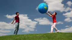 Man and woman playing big inflatable ball on a meadow Stock Footage