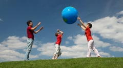 Parents and son playing big inflatable ball on meadow - stock footage