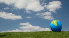 Young lady coming to globe looking ball on meadow Stock Footage