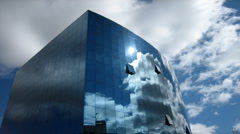 Clouds flying over a glassy modern office building Stock Footage