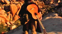 Cowboy Carrying Guitar Climbs Desert Mountain 1 Stock Footage