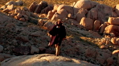 Cowboy Carrying Guitar Climbs Desert Mountain 7 Stock Footage