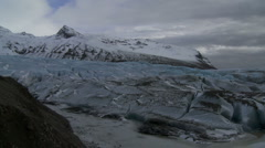 Slow pan across a vast glacier, rugged mountains in the distance. Stock Footage