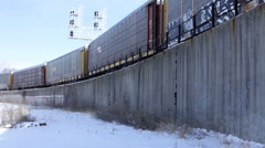 Cargo train driving by with snow on ground Stock Footage