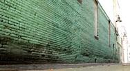 Man running away from and towards camera green brick Stock Footage