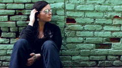 Girl with reflective sunglasses looking down alley Stock Footage