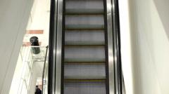 Female riding down escalator Stock Footage