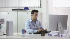 Overworked businessman typing on computer in office Stock Footage