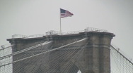 Zoom out from flag on Brooklyn Bridge Stock Footage