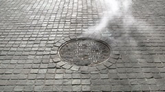 Steam rises from a manhole cover on a cobbled street in New York Stock Footage