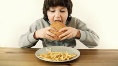 Young happy boy eating fast food, hamburger and french fries, isolated Stock Footage