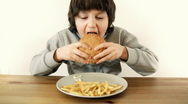 Stock Video Footage of Young happy boy eating fast food, hamburger and french fries, isolated