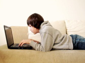 Young boy lying on sofa with laptop Stock Footage