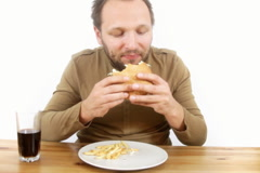 Stock Video Footage of Happy man eating fast food, hamburger and french fries and drinking cola