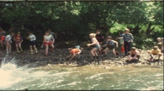 Kids throwing stones in river, 1960s (vintage 8 mm amateur film) - stock footage
