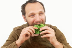 Happy man eating healthy food, vegetables, isolated - stock footage