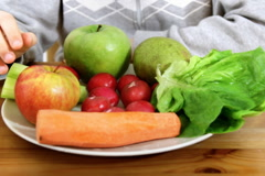 Kids hands taking healthy food, vegetables and fruits from the plate Stock Footage