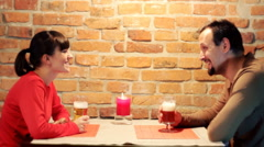 Couple on romantic date in the pub talking and drinking beer - stock footage