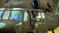 Pilot climbs out of blackhawk helicopter Stock Footage