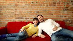 Young happy couple lying on red sofa Stock Footage