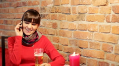 Attractive woman drinking beer and talking on mobile phone - stock footage