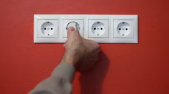 Man unplug and push electric plug into the socket - stock footage