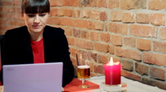 Woman sitting in the pub and working on laptop  Stock Footage