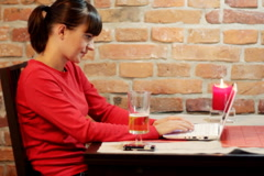 Woman sitting in the pub drinking beer and working on laptop Stock Footage