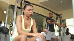 Female drinking water and male working out in gym Stock Footage