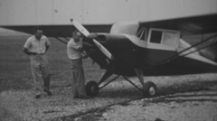 Two Men look over a vintage airplane in the 1950's Stock Footage