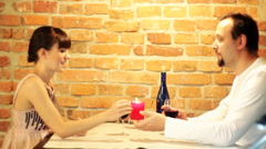 Young happy couple in love talking and drinking wine in restaurant - stock footage