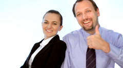 Young smiling business people showing thumbs up sign, isolated Stock Footage