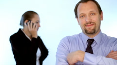 Happy businessman looking to the camera, businesswoman with cellphone in bg Stock Footage