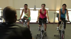Spinning class with male coach in gym - stock footage