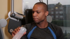 Male having a break and drinking water in gym Stock Footage