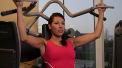 Female working out in gym on exercise machine Stock Footage