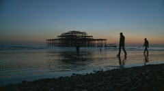 Walkers pass the old pier Stock Footage
