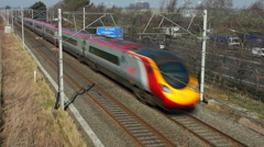 Pendolino passenger train on the West Coast mainline travels beside M1 motorway Stock Footage