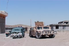 Humvee next to an Afghan army car blown up by IED in Afghanistan NTSC Stock Footage