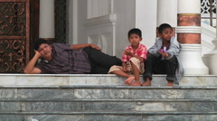 Men and boys rest outside Mosque Stock Footage