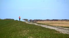 Biking on dike, North Sea, Germany Stock Footage