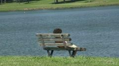 Kid Sitting On Bench At Lake Stock Footage