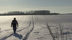 Man walks along snow covered track. - stock footage