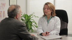 Female doctor meeting with male patient in office - stock footage
