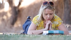 Woman Praying over Bible Stock Footage