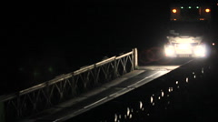 Truck crossing a Bailey Bridge at night Stock Footage