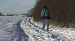 Man with rucksack walks on snow covered track. Stock Footage
