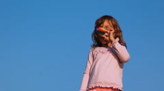 Little girl blows in party blower on sky Stock Footage