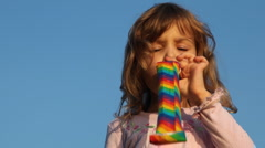 Little girl blows in party blower facing camera Stock Footage