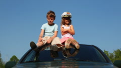 Boy and girl sit on roof of car Stock Footage